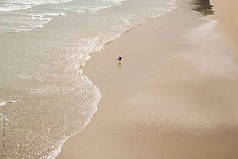 Surfer on big empty beach by Gary Parker for Stocksy United