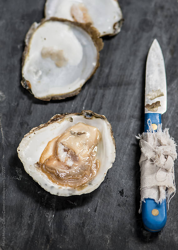 Oysters on blackboard with knife opener by Marta Muñoz-Calero Calderon for Stocksy United