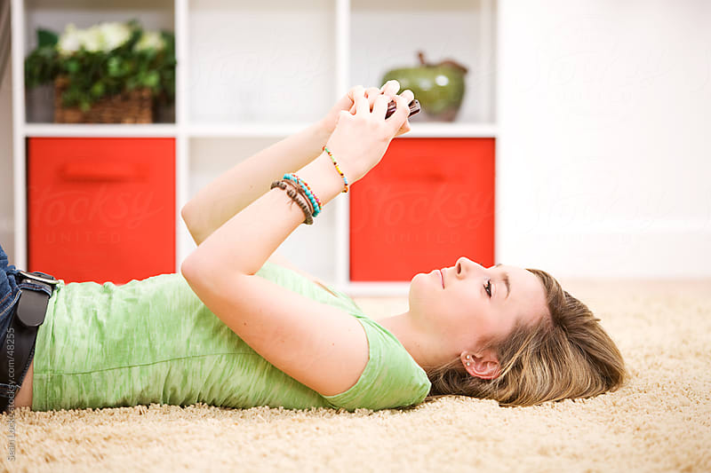 Teens: Girl Texting on the Floor by Sean Locke for Stocksy United