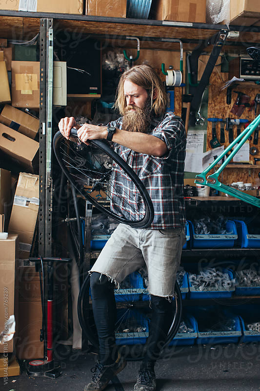 Long-Haired Hipster Mechanic Assembling Fixie in Bright Bike Workshop by VISUALSPECTRUM for Stocksy United