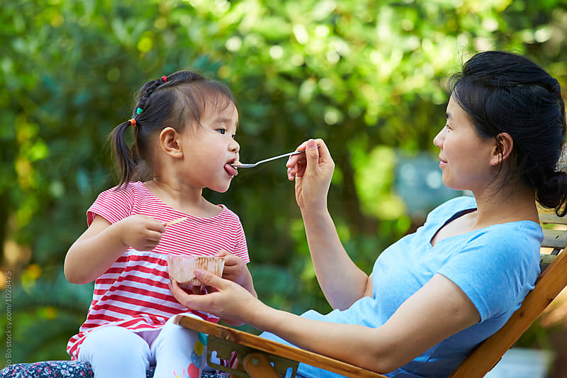 happy little asian girl eating ice cream with her mother in the yard by Bo Bo for Stocksy United
