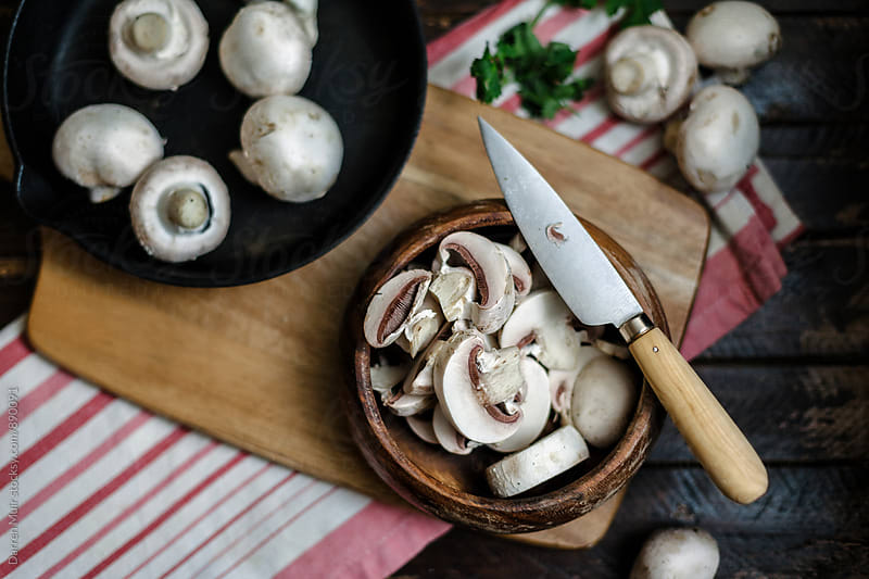 Sliced mushrooms in a wooden bowl on a cutting board. Seen from overhead. by Darren Muir for Stocksy United