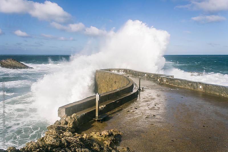 Wave splashing against a dock by Alejandro Moreno de Carlos for Stocksy United