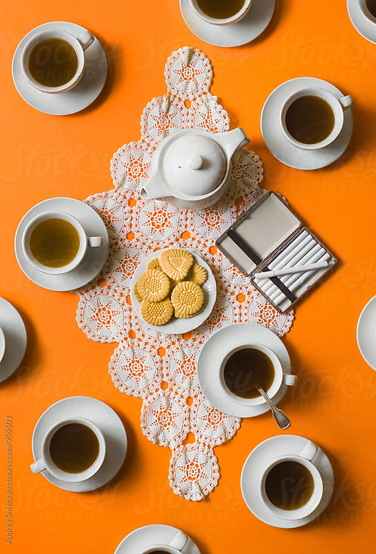 Coffee cups with cookies on tablecloth on orange background / ook from above by Audrey Shtecinjo for Stocksy United