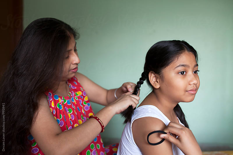 Indian woman tying hair of her daughter by PARTHA PAL for Stocksy United