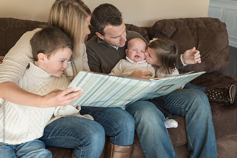 Sister Kisses Brother As They Look At Photo Album by Alison Winterroth for Stocksy United