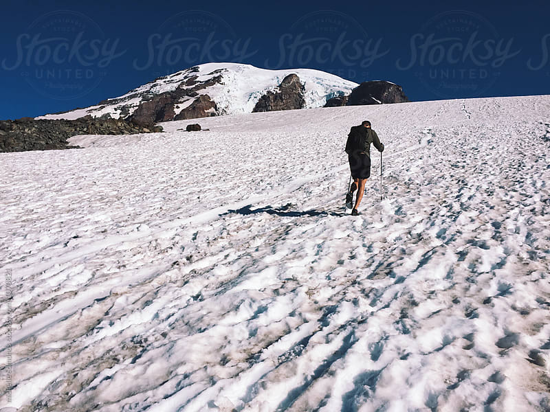 Male Hiker Climbing up Snowy Mountain by michelle edmonds for Stocksy United