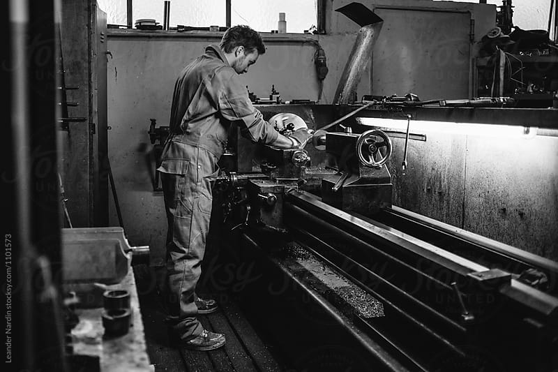 metal worker working with a engine lathe - black and white by Leander Nardin for Stocksy United