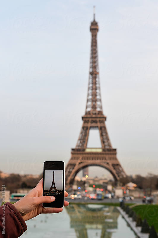 Woman taking photos with a smartphone to the Eiffel Tower, Paris by Bisual Studio for Stocksy United