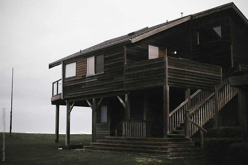 beach house at the coast on gloomy day by Nicole Mason for Stocksy United
