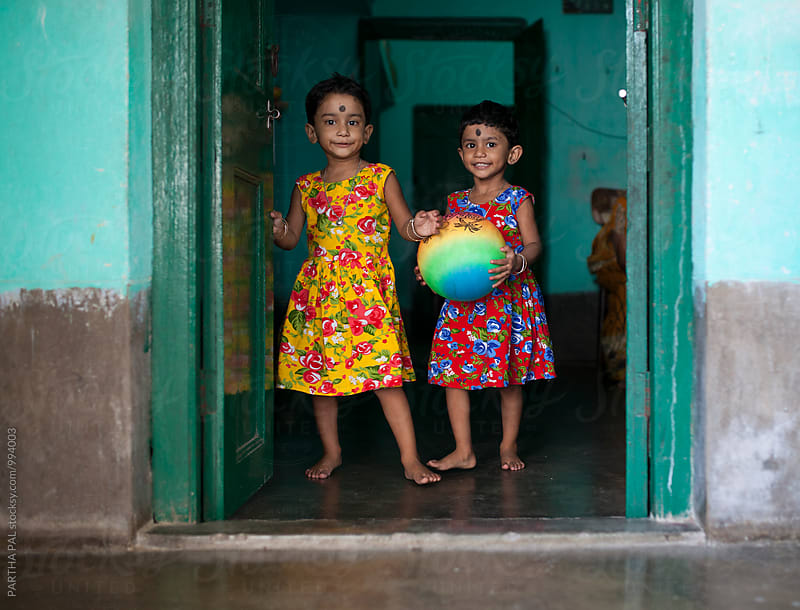 Indian twin girl wuith playing ball and standing together by PARTHA PAL for Stocksy United