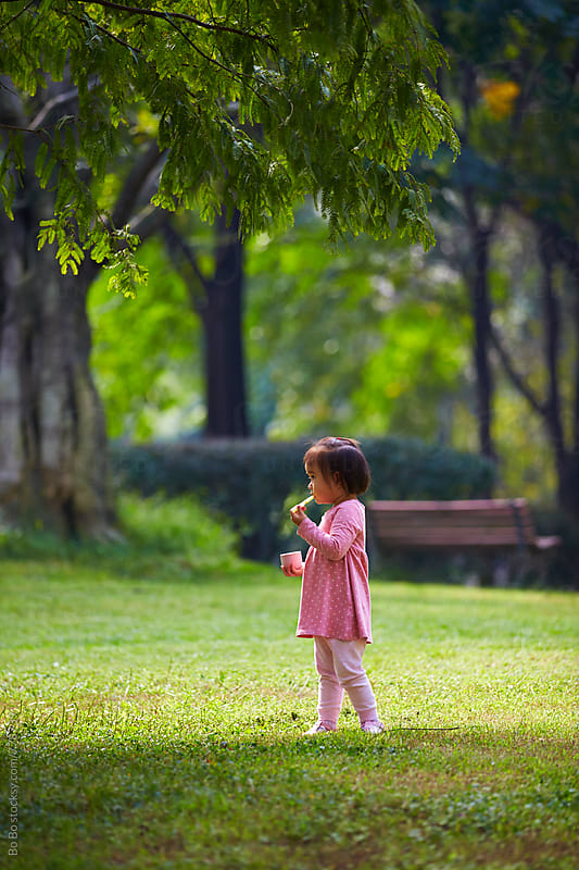 one lovely little asian girl in the park  by Bo Bo for Stocksy United