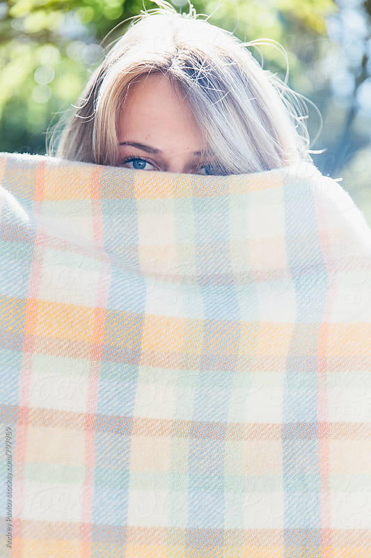 Woman hiding in a checkered blanket by Andrey Pavlov for Stocksy United