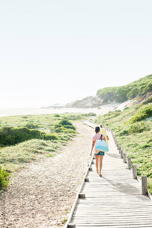 Girls on Holiday heading to the beach by Aila Images for Stocksy United