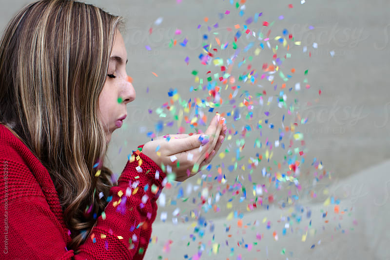 Beautiful teenage girl having fun with confetti by Carolyn Lagattuta for Stocksy United