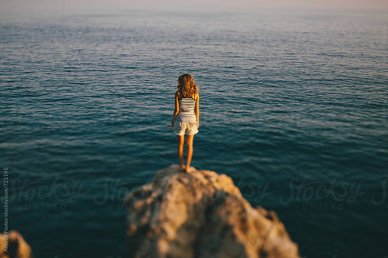 Woman standing on a cliff by Andrey Pavlov for Stocksy United