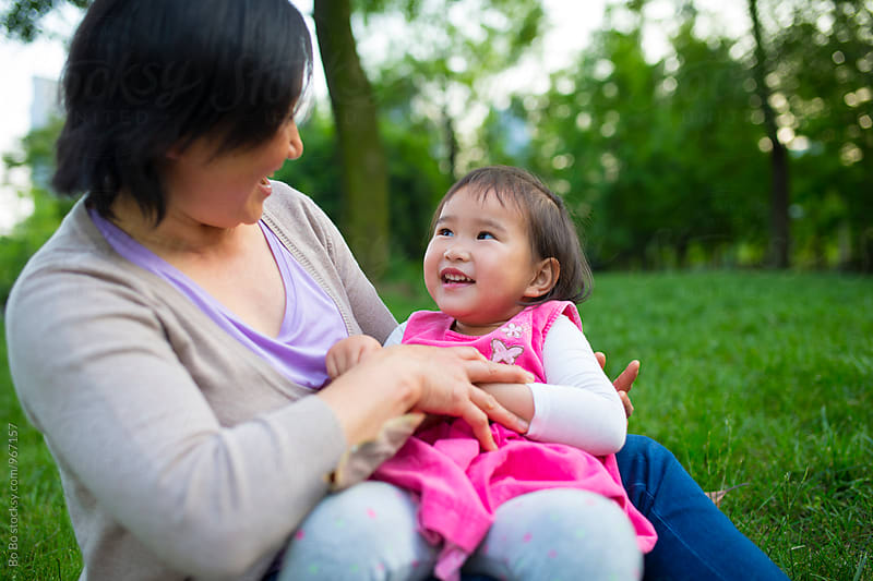 lovely little asian girl having good time outdoor with her grandmother by cuiyan Liu for Stocksy United