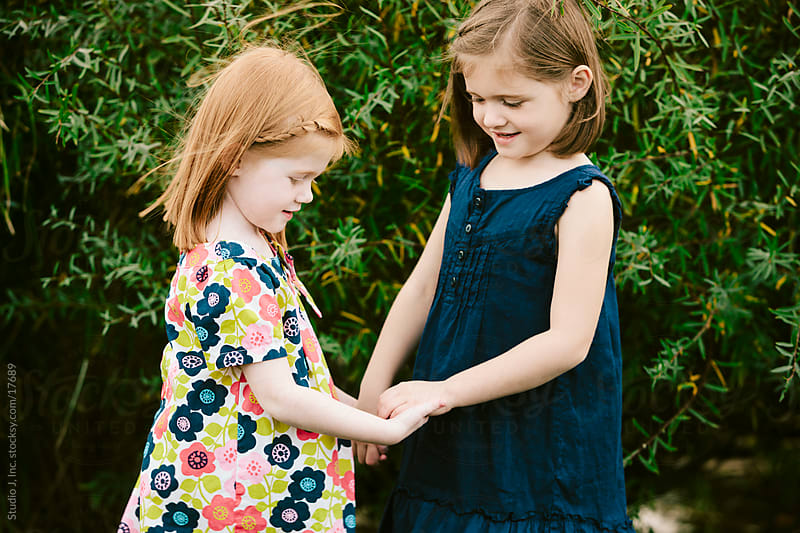 Little Girl Sisters Hold Hands Outside by Studio J, Inc. for Stocksy United