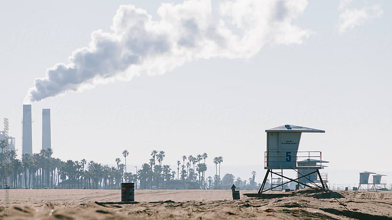 Beach, sand, lifeguard towers and steam power plant in southern california by Emmanuel Hidalgo for Stocksy United