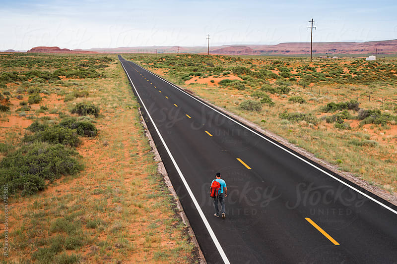 Man Walking Down Remote Asphalt Highway Extending to Horizon in Arizona by JP Danko for Stocksy United