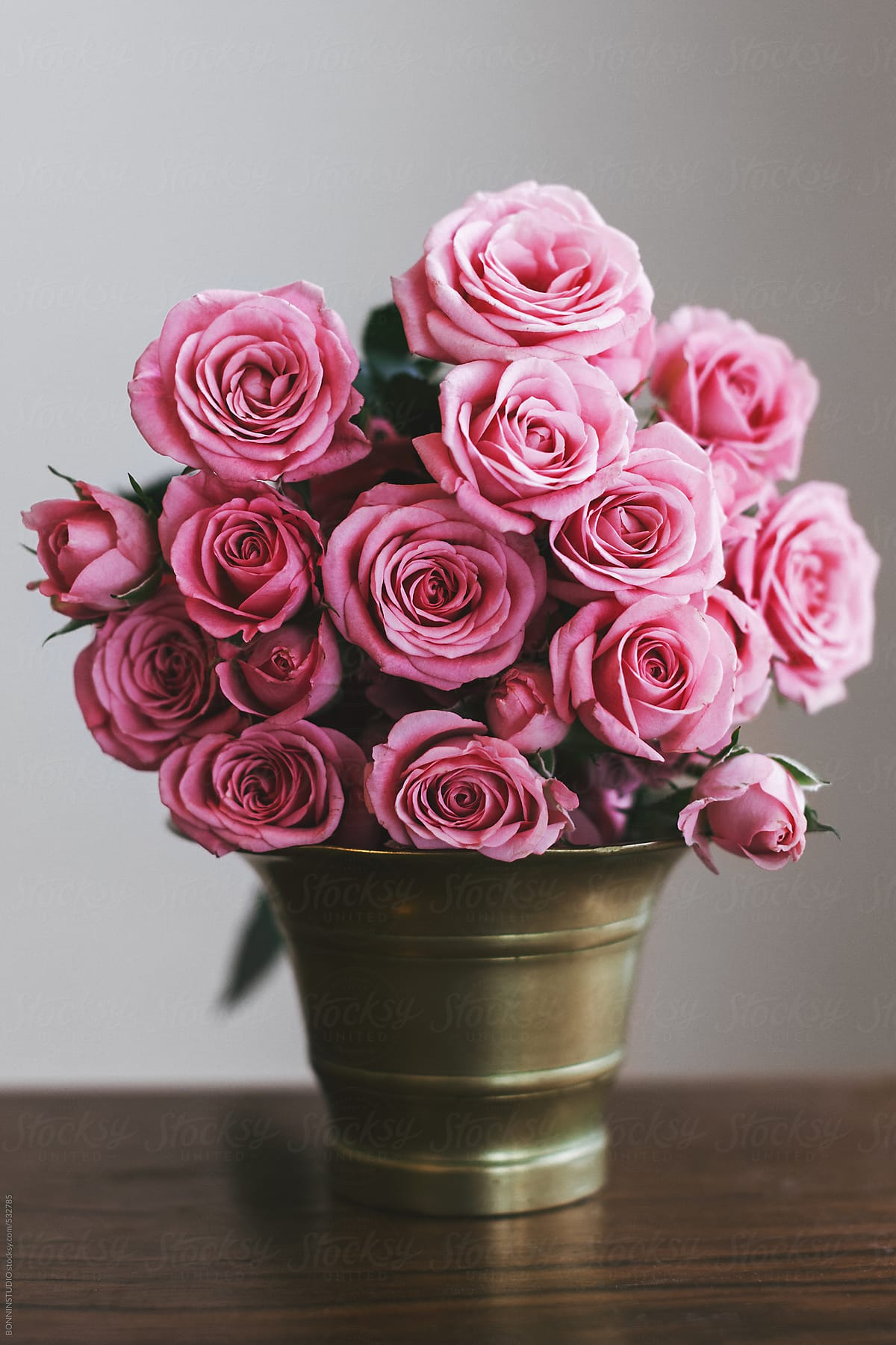 Bouquet of a pink roses in a vintage gold vase on a wood table bouquet of a pink roses in a vintage gold vase on a wood table by izmirmasajfo