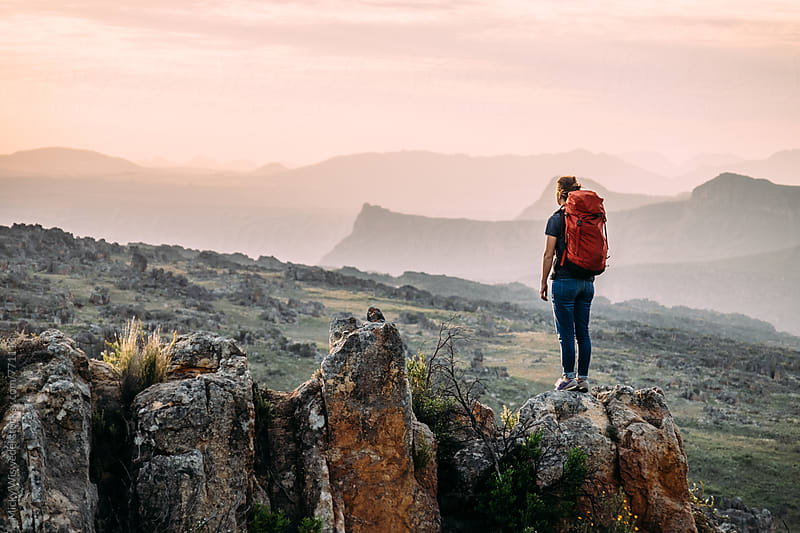 Female hiker with a backpack in rugged mountain terrain at sunset by Micky Wiswedel for Stocksy United