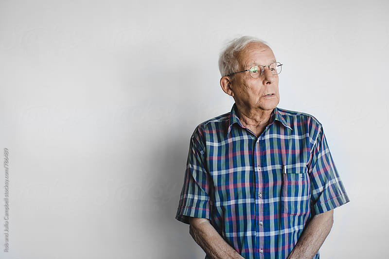 Serious older man on white studio background by Rob and Julia Campbell for Stocksy United