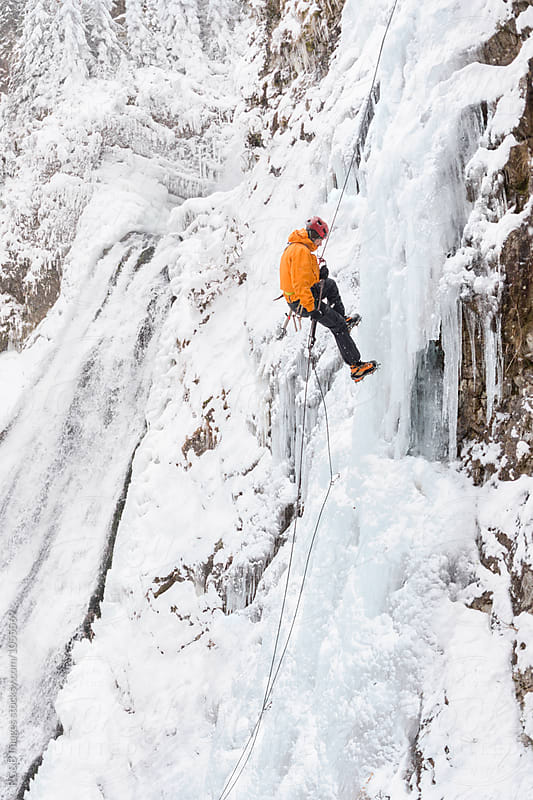 Male climber descending on a frozen waterfall by RG&B Images for Stocksy United