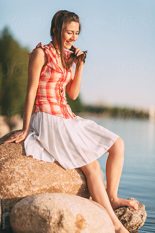 Young happy smiling woman sitting near water by Ilya for Stocksy United