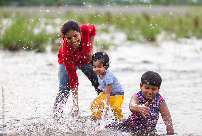 Family enjoying hot summer day in the river by Saptak Ganguly for Stocksy United
