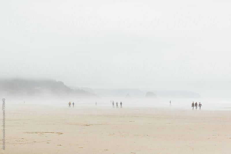 People walking on the beach in a foggy day by michela ravasio for Stocksy United