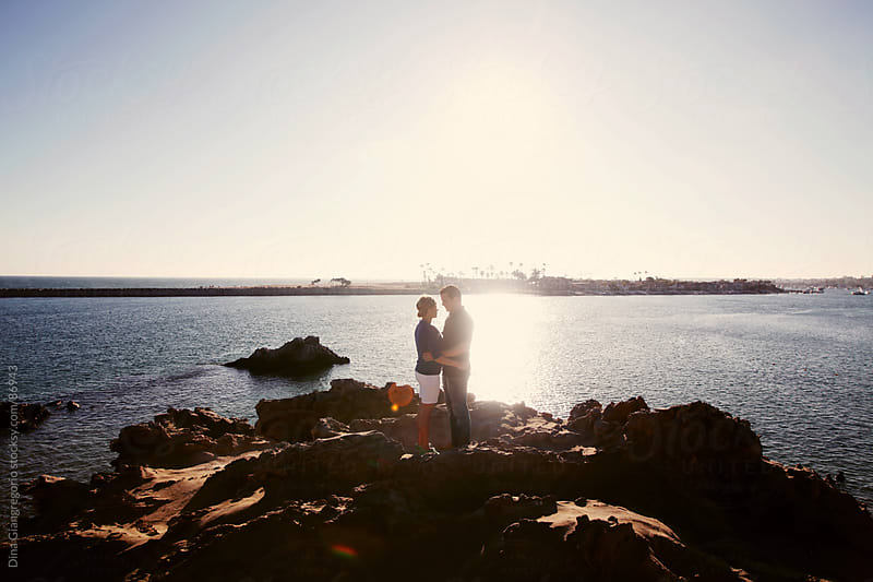 Wide angle silhouette shot of couple standing on rocks at a beach by Dina Giangregorio for Stocksy United