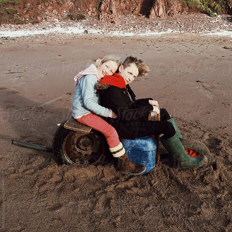2 children sitting on a motorbike that they have made from junk washed up on a beach by Helen Rushbrook for Stocksy United