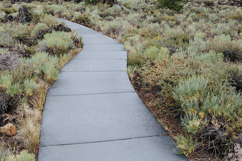 Paved hiking trail through sagebrush and lava field by Paul Edmondson for Stocksy United