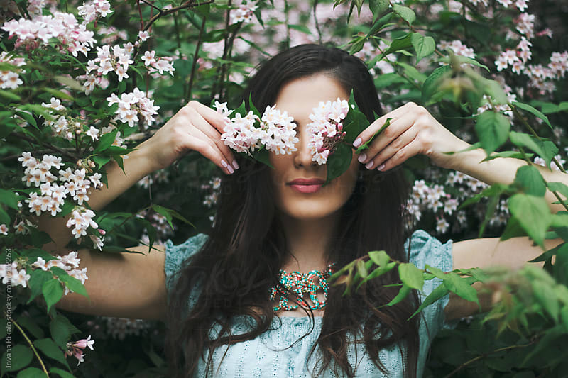 Beautiful young woman hiding her eyes with flowers by Jovana Rikalo for Stocksy United