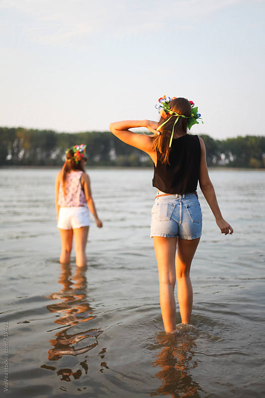 Twom stylish female friends standing in the river during the sunset by Marija Mandic for Stocksy United