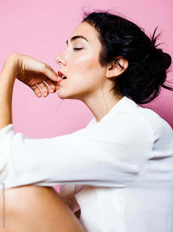 Side profile of woman biting her nails by Kayla Snell for Stocksy United