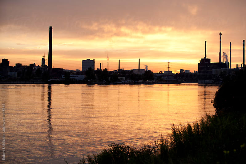Industrial factory at dusk by Robert Kohlhuber for Stocksy United