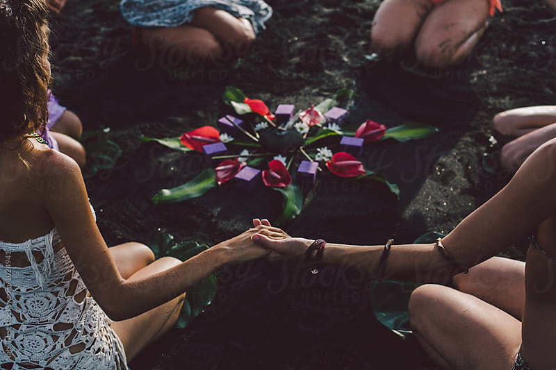 Women on the beach join hands around the flower mandala by Nabi Tang for Stocksy United