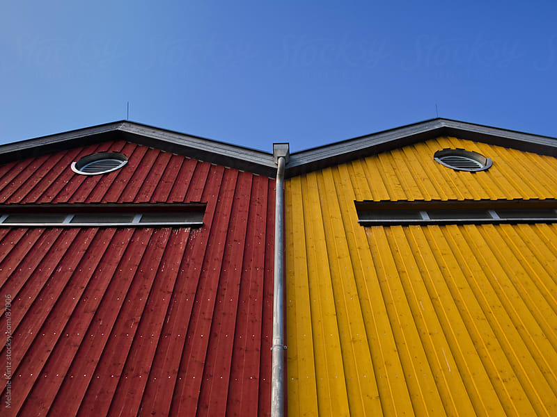Red and Yellow house before blue sky by Melanie Kintz for Stocksy United
