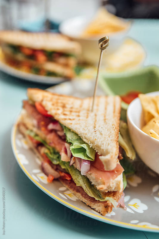Food: Sandwich Toast with salmon, tomato, onions and salad  by Ina Peters for Stocksy United