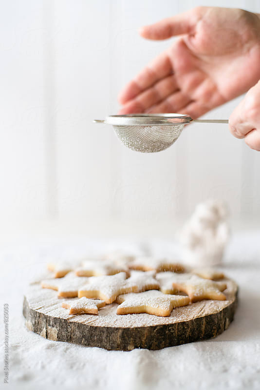 Dusting cookies with powdered sugar by Pixel Stories for Stocksy United
