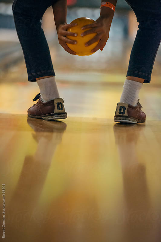 Child Bowling With Two Hands by Ronnie Comeau for Stocksy United