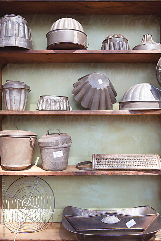 a collection of old tin kitchen moulds, pans and trays for sale at a vintage flea market by Natalie JEFFCOTT for Stocksy United