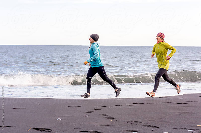 Two female runners running on black beach in Iceland by Soren Egeberg for Stocksy United