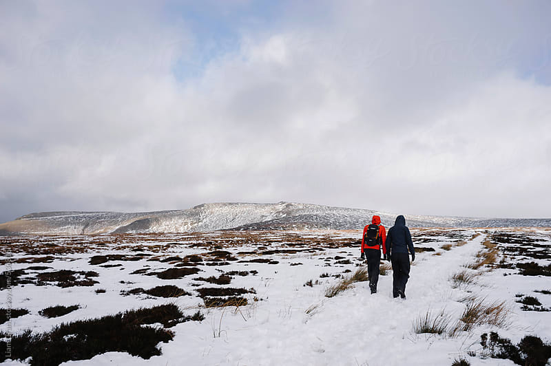 Young couple exploring the snow covered moorland of Bleaklow. by Liam Grant for Stocksy United