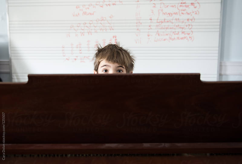 Boy peeks over the top of a grand piano during his music lesson by Cara Dolan for Stocksy United