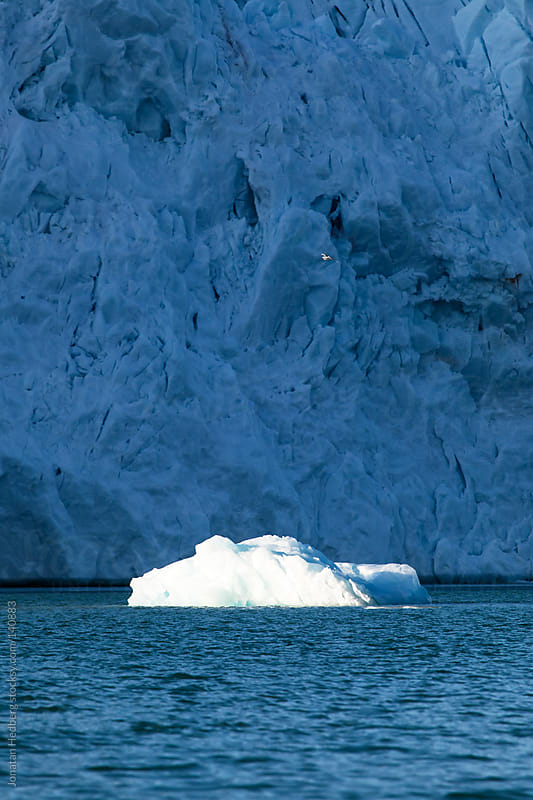 A smaller piece of ice floating in front of a glacier by Jonatan Hedberg for Stocksy United