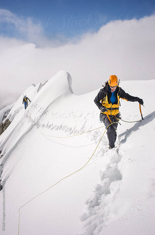 Mountaineers walking along a norrow snow ridge by RG&B Images for Stocksy United