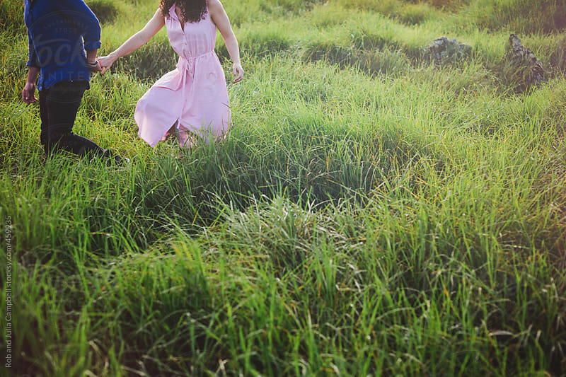 Lower half of couple walking together in lush grass by Rob and Julia Campbell for Stocksy United